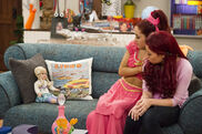 Sam and Cat sitting with a doll