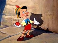 Pinocchio holds an apple