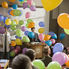 Balloons fall down in the lecture hall.