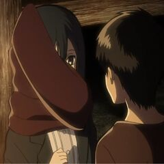 Eren le da su bufanda a Mikasa.