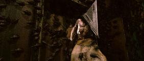 Pyramid Head as he retreats as Cybil shoots his hand.