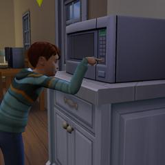 Un niño usando el microondas.