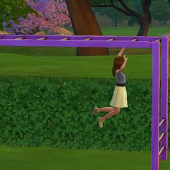 Una niña jugando en las barras paralelas.