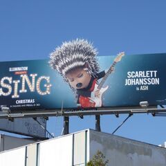 Ash appears on a billboard promoting <i>Sing</i> (location unknown)