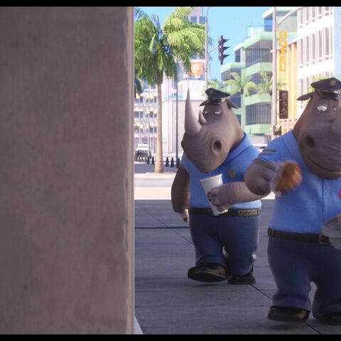 The officers enjoying donuts and beverages walking past the ally where <a href=