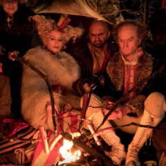 Count Olaf, Esmé and Count Olaf's Troupe beside a fire.