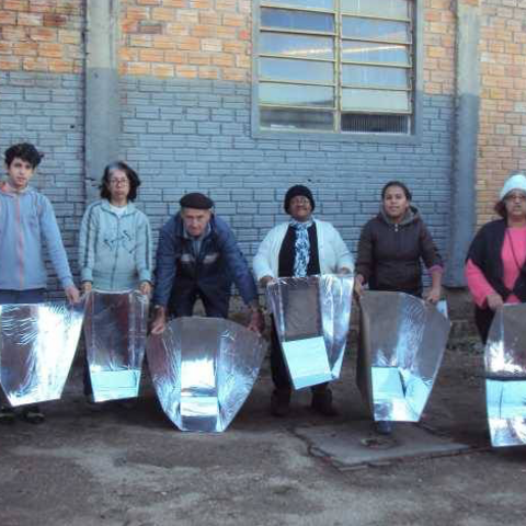 Morro da Cruz particpants proudly display their recently constructed solar panel cookers. <i>Photo credit: <a href=