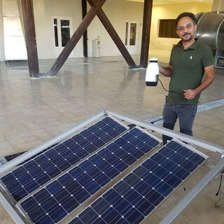 Amir holds a coffeemaker that he reports boils water with energy generated with the accompanying PV panels - <i>Photo credit: Amir Komarizade</i>]]