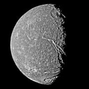 A round spherical body with its left half illuminated. The surface has a mottled appearance with bright patches among relatively dark terrain. The terminator is slightly to the right from the center and runs from the top to bottom. A large crater with a central pit can be seen at the terminator in the upper half of the image. Another bright crater can be seen at the bottom intersected by a canyon. The second large canyon runs from the darkness at the lower-right side to visible center of the body.