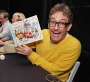Tom Kenny with cast poster