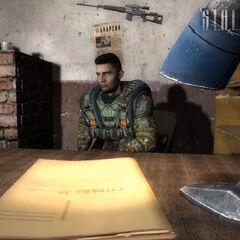Loki siedzi przy biurku (w tle jego karabin snajperski)