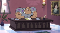 S3E17 Muscular castle staff member behind a desk