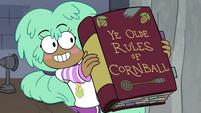 S4E16 Kelly holding Rules of Cornball book
