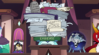 S3E29 Moon holding a large pile of evidence