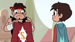S3E13 Sensei holding a cape with an emblazoned 'S'