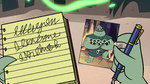 S2E20 Buff Frog looking at photo of himself and tadpoles
