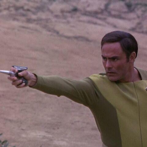 Human firing a needler pistol