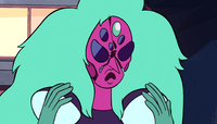 Alexandrite frowns, hands raised, as her face begins to crack apart.