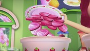 Strawberry is adding some strawberries to her batter