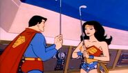 Superman and Wonder Woman holding golf clubs