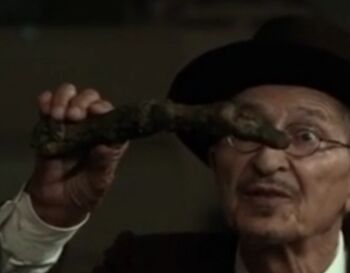 Mr. Vili holding Ymir's finger bone