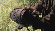 Dean holding Castiel's trenchcoat