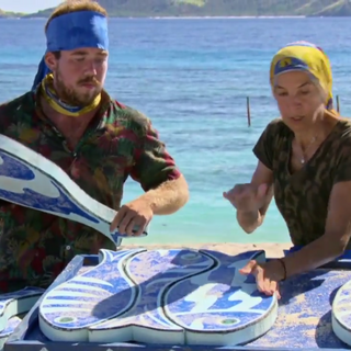 The blue team works on their puzzle (<i>Game Changers</i>).