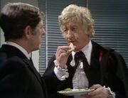 The Doctor eats sandwiches holding plate