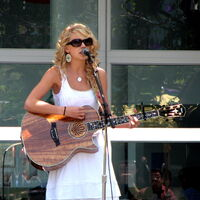 A blond female, clothed by a white sundress and large sunglasses, in a semi-right profile view playing a wooden acoustic guitar. Behind her appears a window in daylight.