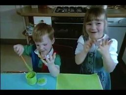 The two children make paintings of fish with their hands