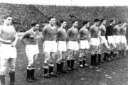 A black-and-white photograph of a football team lining up before a match. Eleven men in old-fashioned association football attire stand in a line: ten wear dark shirts, white shorts and black socks, and the other wears a still darker shirt. Behind the players can be seen one of the enormous open stands of an East European-style soccer stadium, filled to the brim with spectators.