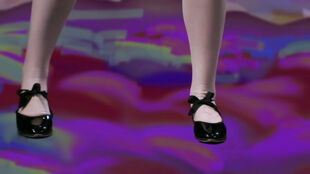 Eagle Lady wears white tights in black tap shoes with bow ties