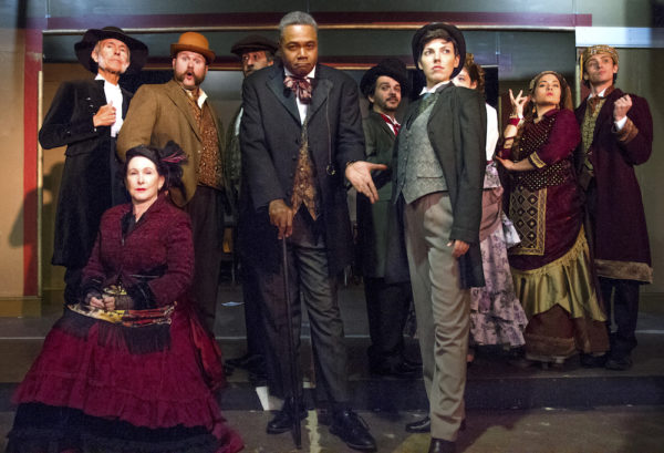 Darryl Maximilian Robinson as The Chairman Mr. William Cartwright & Mayor Thomas Sapsea ( center-left ) and Sarah Myers as Edwin Drood & Miss Alice Nutting ( standing right ) with Suspects in The Mystery of Edwin Drood.