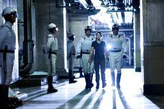 Katniss siendo escoltada por Agentes de la Paz