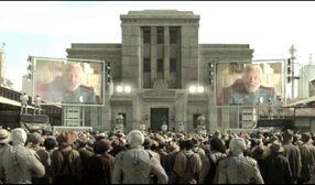 Жители Панема слушают телеобращение президента Сноу
