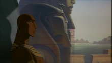 Rameses in his thrown room with his and his father's statue behind him