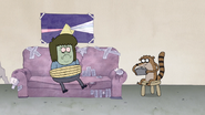 S4E12.119 Rigby Playing a Video Game While Watching Muscle Man