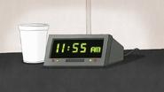 S7E25.057 Clock on Muscle Man's Desk