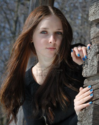 File:2785475-teenage-girl-in-black-with-sunny-face-and-long-waved-hair-looks-near-timber-wall-of-old-country-hous.jpg