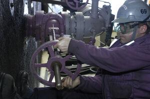 USN sailor operates fuel valve · 070115-N-9479M-004