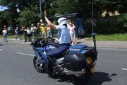 Gendarmerie motor officer raising arm in traffic