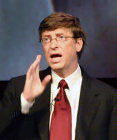Head and shoulders portrait of talking 50-year-old man in rimless glasses, business suit, and power red tie, with raised right hand gesturing.