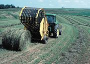 John Deere tractor with round baler in Iowa