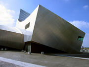 A metal-clad building with both angular and curved surfaces, with a rectangular window on one side.