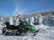 A snowmobile on a snowy mountain.