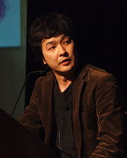 A Japanese man in a brown jacket and dark grey shirt standing at a podium