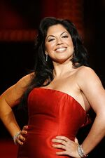 Sara Ramirez posing for the camera in a red dress