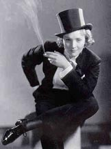 Black-and-white image of a young woman wearing a tuxedo-like suit and top hat. She sits with her right leg, almost parallel to the ground, over her left knee. She leans forward and gazes out directly with a tight-lipped smile. In her right hand she holds a cigarette from which a large plume of smoke rises.