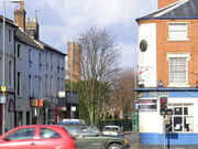 The corner of a street with a public house called The Ivy Bush on the right side. In the background two tall brick towers can be seen further left.