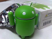 Android green figure, next to its original packaging
